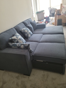 A dark blue couch with pillows on it is popped out to a full sized bed.